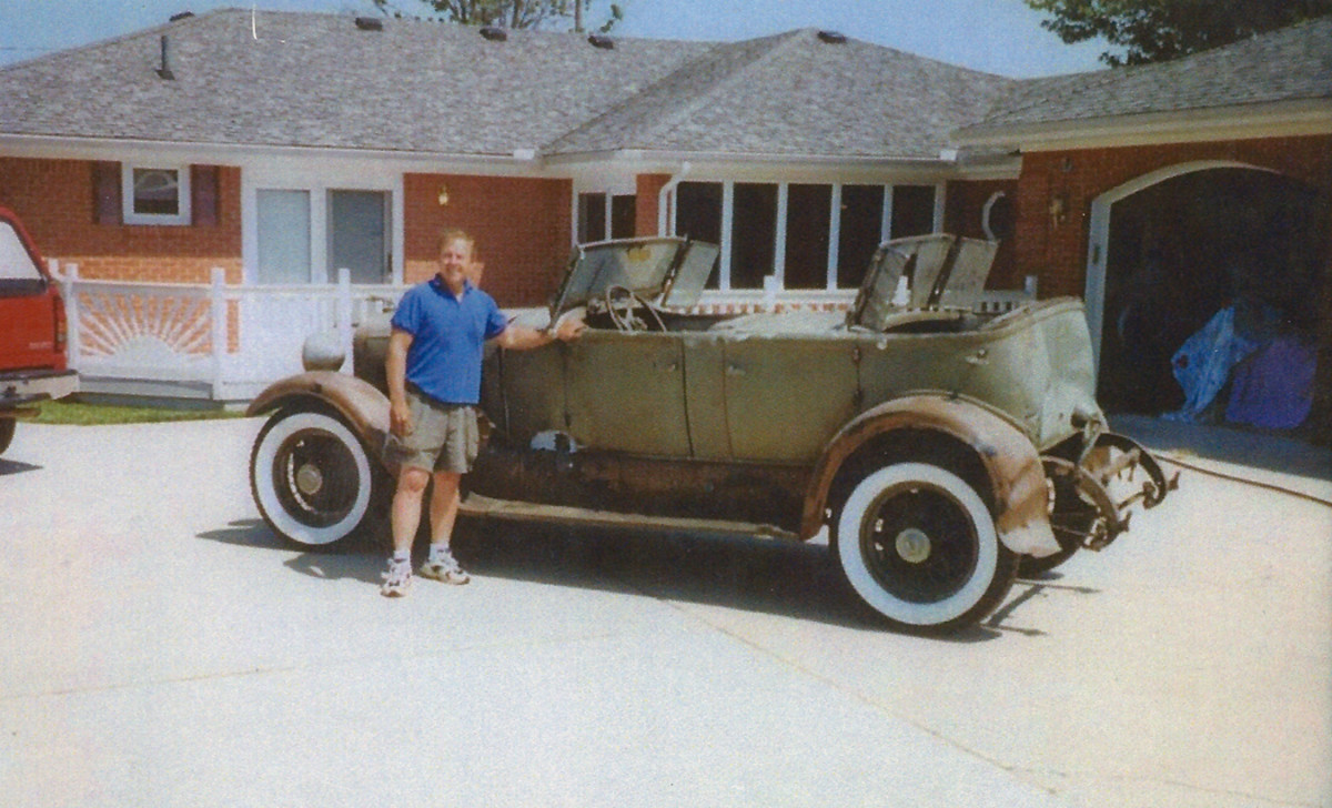 William Kendall and the 1930 Lincoln Model 176-B Tonneau Cowl Sport Phaeton as it was found in 2005 after decades of storage. The rear of the body and the back fenders, frame horns and springs were damaged from striking a police car in a long-ago get-away.