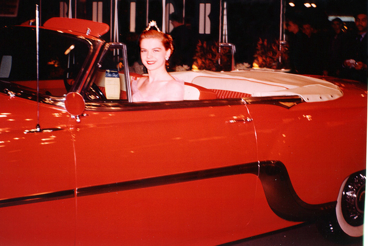 """As Miss Berwyn-Cicero, June poses behind the steering wheel of a 1954 Pontiac Star Chief convertible just moments before she would be chauffeured on to the stage during the CAS's """"Wheels of Progress"""" revue."""